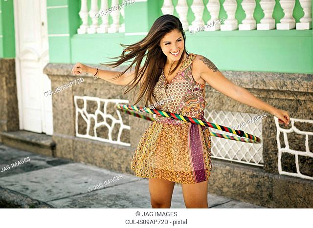 Student celebrating, demonstrating hula hoop skills in the street, Rio de Janeiro, Brazil