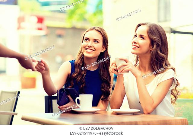 people, consumerism, lifestyle and friendship concept - smiling young women giving credit card to waiter hand and paying for coffee at outdoor cafe