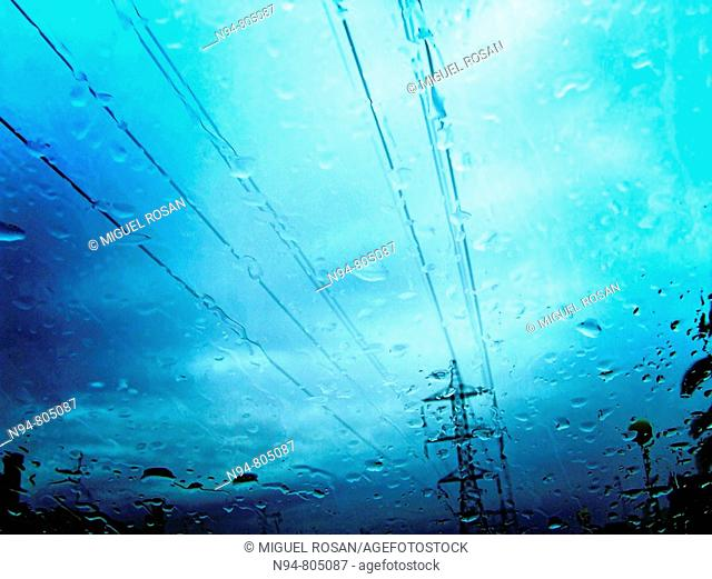 Vista de un poste de suministro de electricidad a través del parabrisas de un coche, en un gris y lluvioso día
