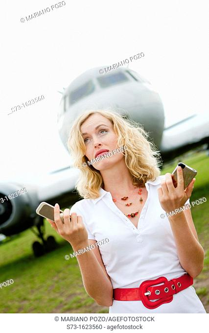A business woman with two mobiles phones next to a plane
