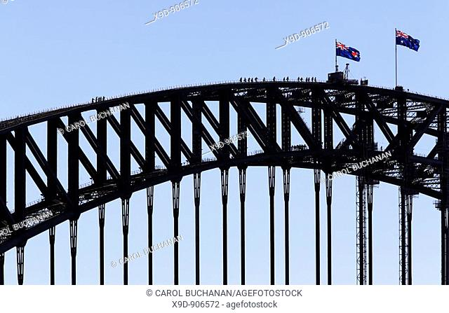 a group of people climbing the Sydney Harbour Bridge with two Australian flags flying