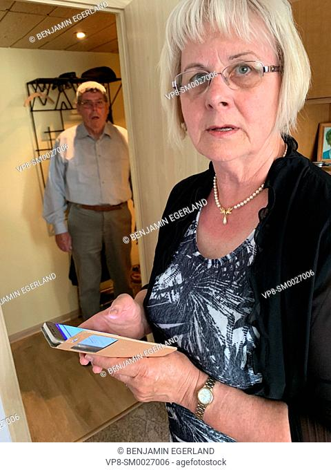 confused senior woman holding smartphone at home next to baffled senior husband, in Cottbus, Germany
