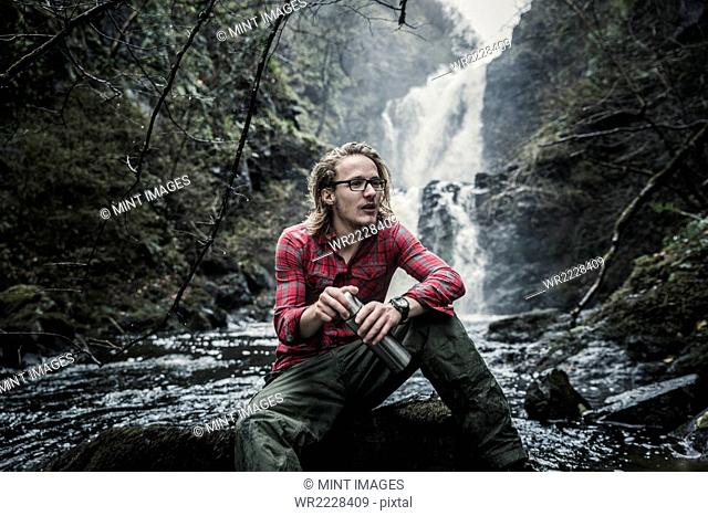 A man sitting on a rock by a waterfall, holding a flask. Winter hiking