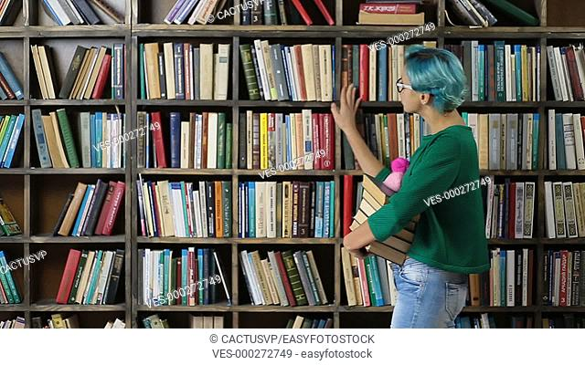 Female student choosing book on shelf in library
