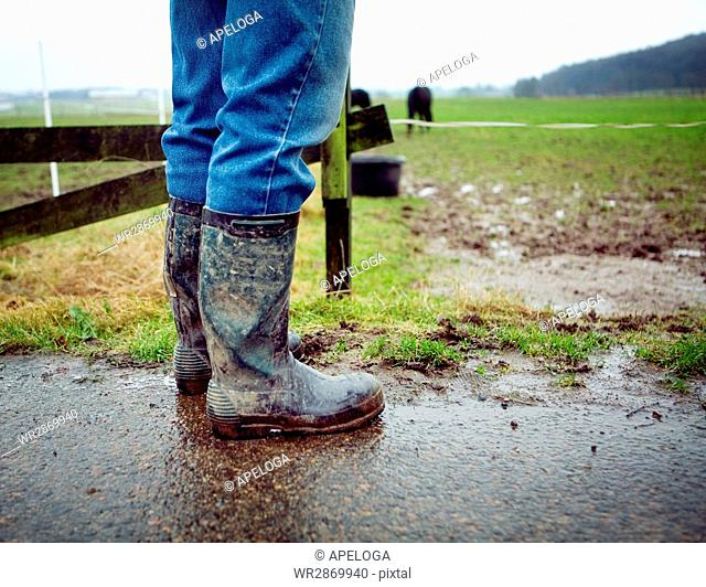 Low section of person in messy boots standing on field