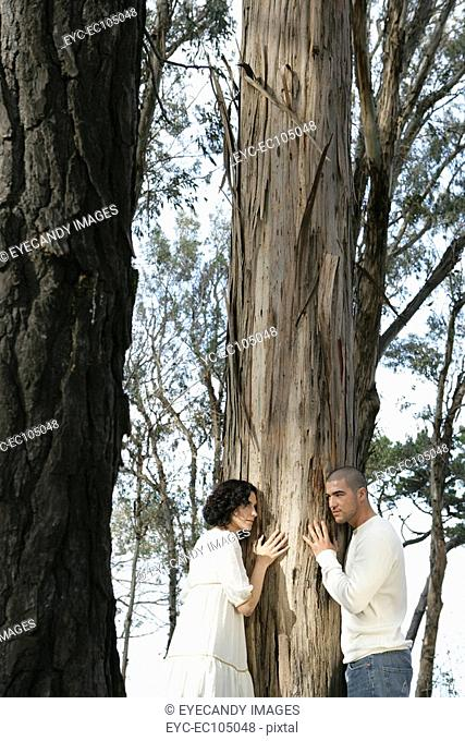 Young couple hugging tree