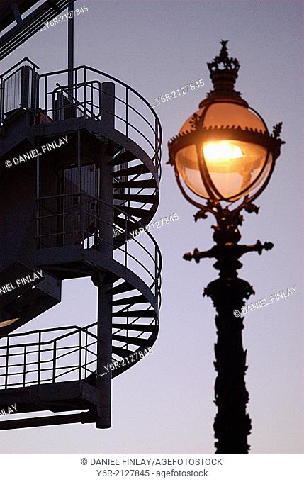 Spiral staircase on the London Eye seen at dusk with an ornate Victorian streetlight in the foreground, in the heart of London, England