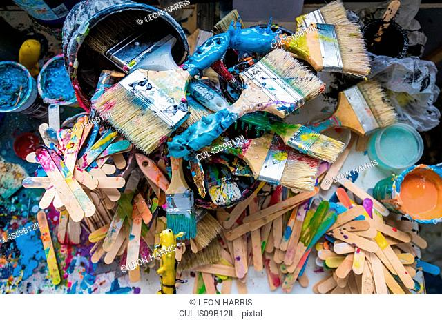 Overhead view of paint brushes and stirrers in surfboard maker's workshop