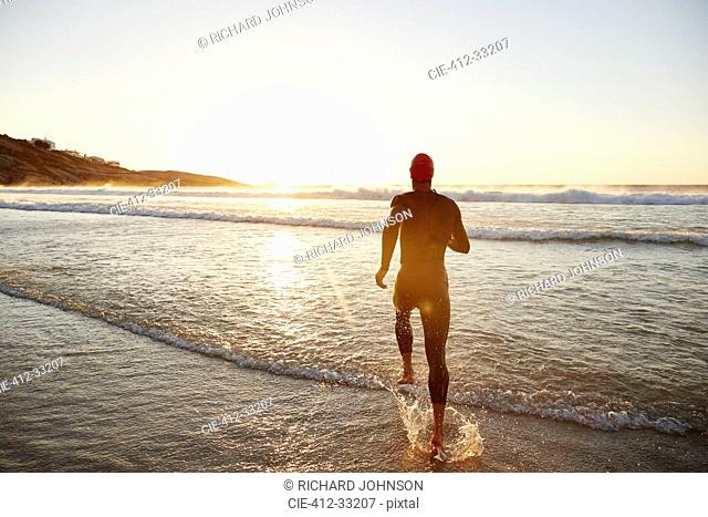 Male triathlete swimmer in wet suit running into ocean surf at sunrise