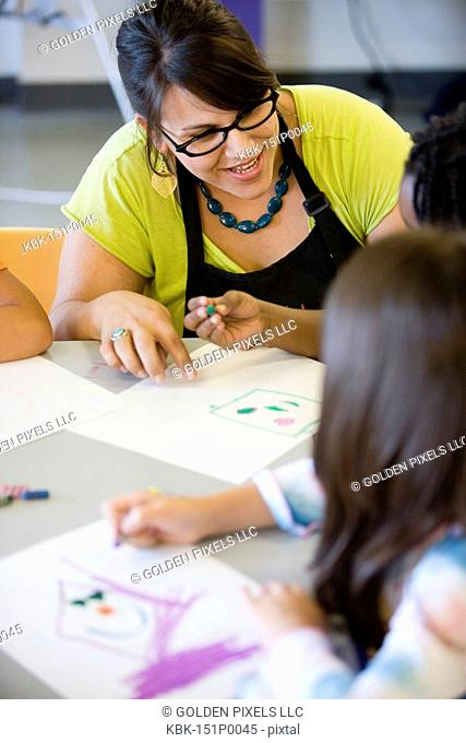 Close up of teacher helping young children in class