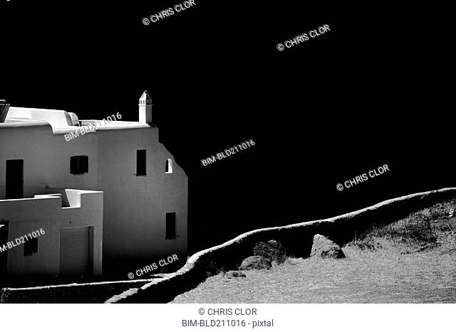 Dirt path and building overlooking coastline