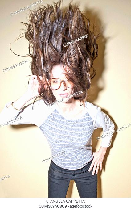Woman wearing sunglasses tossing hair