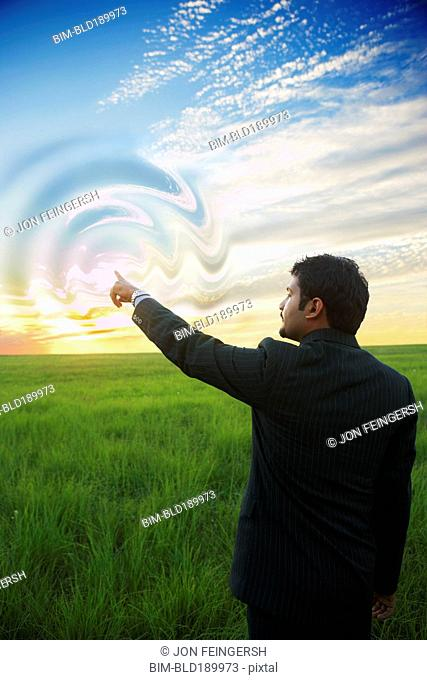 Indian businessman swirling sky with finger