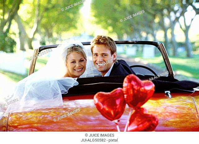 Bride and groom in red convertible, heart shaped balloons tied to bumper