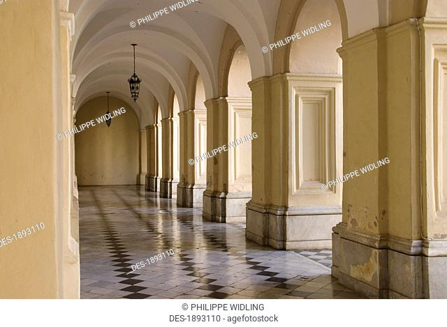 a corridor with tile floors and columns in the manzana jesuitica, cordoba, argentina