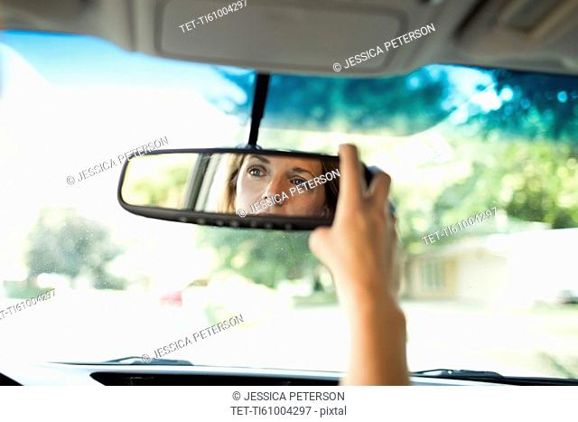 Woman adjusting rear-view mirror in car