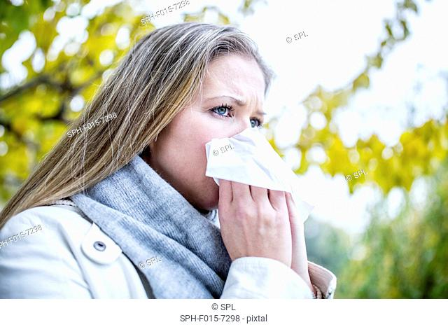 MODEL RELEASED. Young woman sneezing, close-up