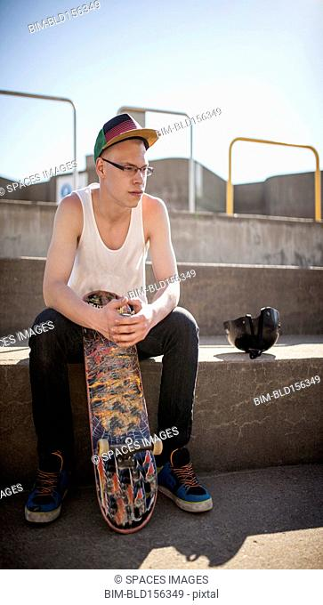 Caucasian man sitting at skate park