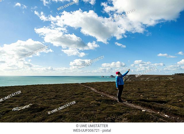 France, Bretagne, Finistere, Crozon peninsula, woman standing at the coast taking a selfie