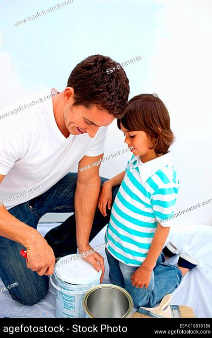 Cute little boy and his father painting a room