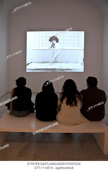 Visitors watching a Buster Keaton movie in the Centro de Arte Reina Sofia, Madrid, Spain