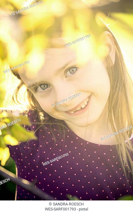 Portrait of smiling little girl looking through twigs of a tree