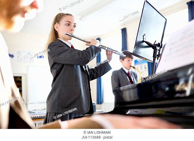 High school student playing flute behind music teacher playing piano