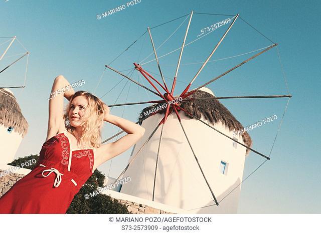 30 year old woman in front of windmill, Mykonos, Cyclades islands, Greece