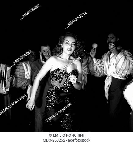 Abbe Lane dances, surrounded by musicians wearing traditional costumes and in front of Xavier Cugat. American actress Abbe Lane, born Abigail Francine Lassman