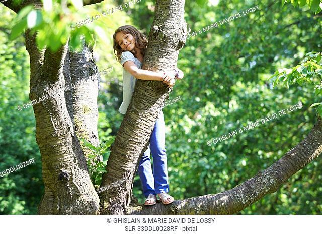 Smiling girl climbing tree outdoors
