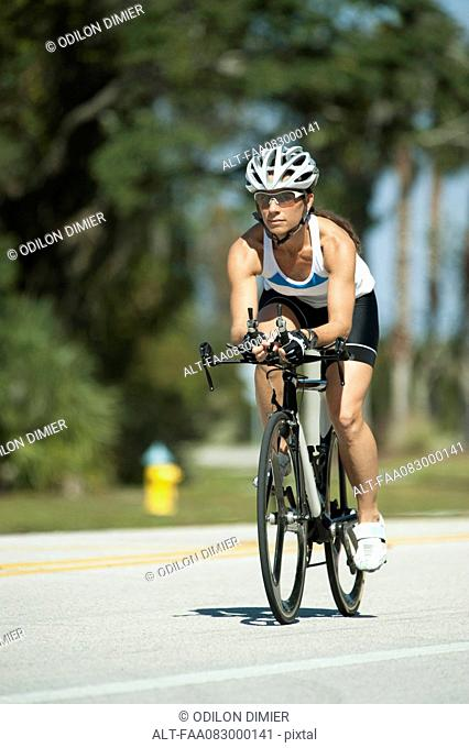 Female cyclist riding on road