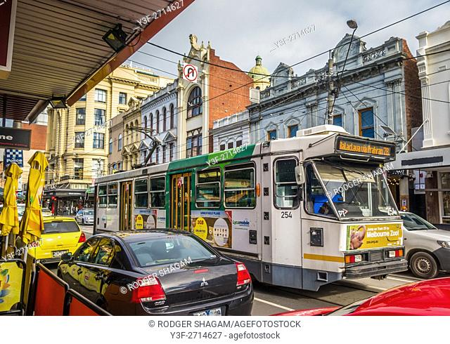 A typical Melbourne high street, showing shops,traffic and a tram