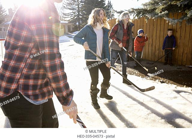 Smiling mothers playing ice hockey in sunny, snowy driveway