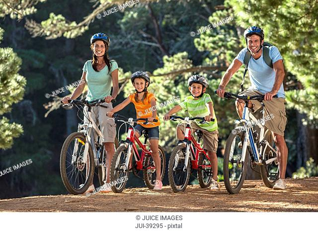 Portrait of smiling family on mountain bikes in woods