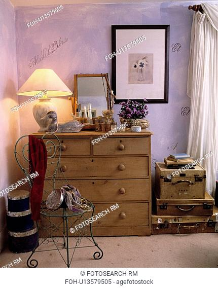 Metal chair and antique pine chest of drawers with lighted lamp in mauve cottage bedroom with old leather suitcases