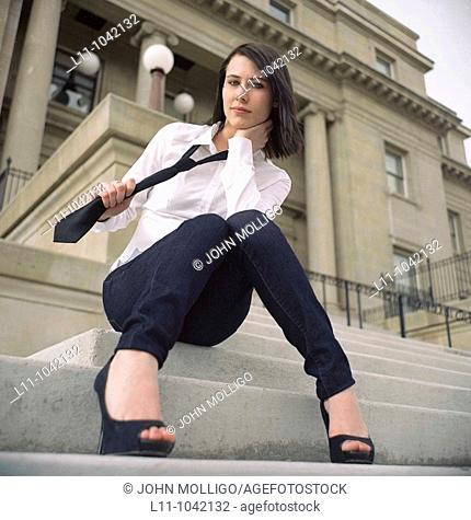 Woman sitting on steps of Public Building pulling on her necktie