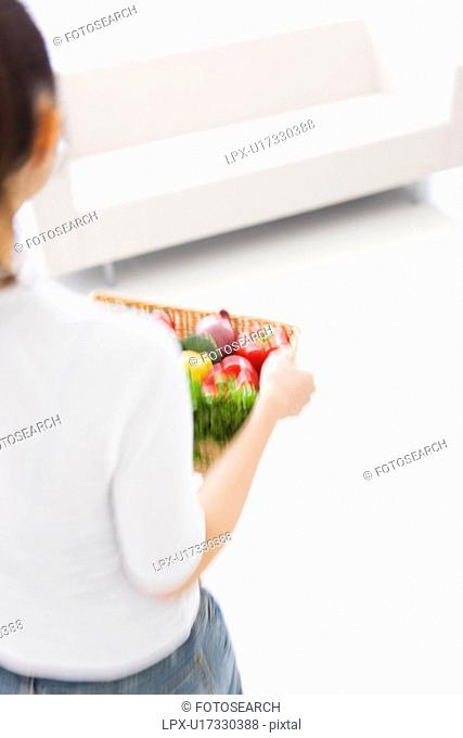 Woman carrying basket with fresh vegetables