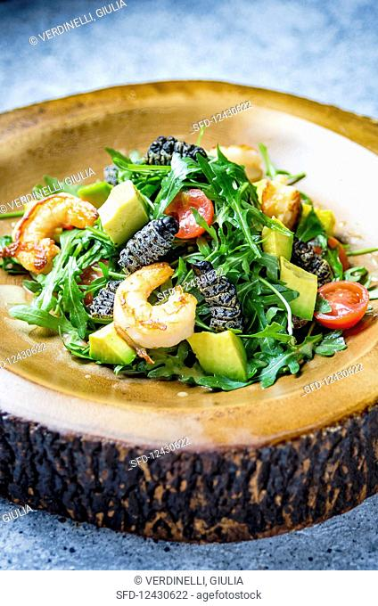 Rocket salad with caterpillars and prawns, avocado, cherry tomatoes on a wooden plate and marble background