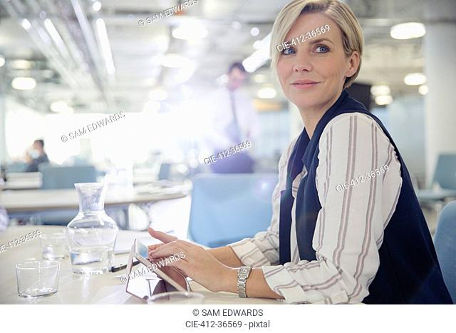 Smiling, confident businesswoman using digital tablet in office meeting