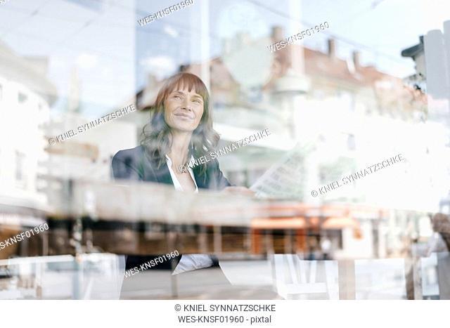 Businesswoman sitting cafe, reading newspaper