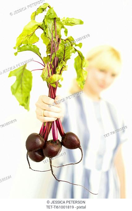 Studio shot of woman holding bunch of beetroots
