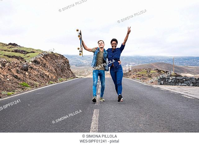 Spain, Tenerife, happy young couple walking on empty road