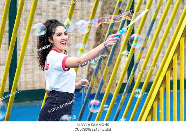 Enthusiastic young woman in playground making bubbles with bubble wand