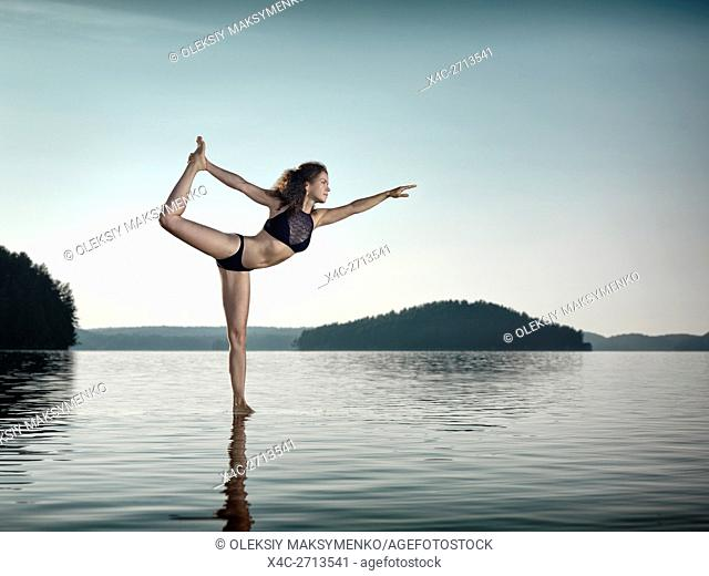 Young woman practicing Hatha yoga on a floating platform in water on the lake during sunrise in the morning. Yoga Dancer posture, Dandayamana Dhanurasana