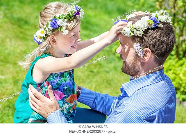 Father with daughter wearing flower wreaths