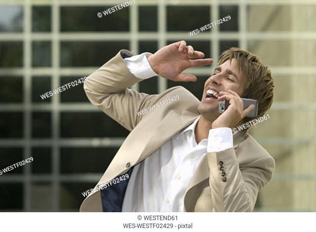 Businessman using mobile phone, laughing, close-up