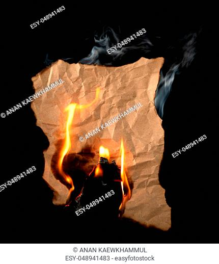 burning piece of crumpled paper on black background