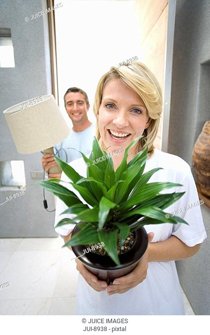 Woman holding pot plant, man holding lamp, smiling, portrait