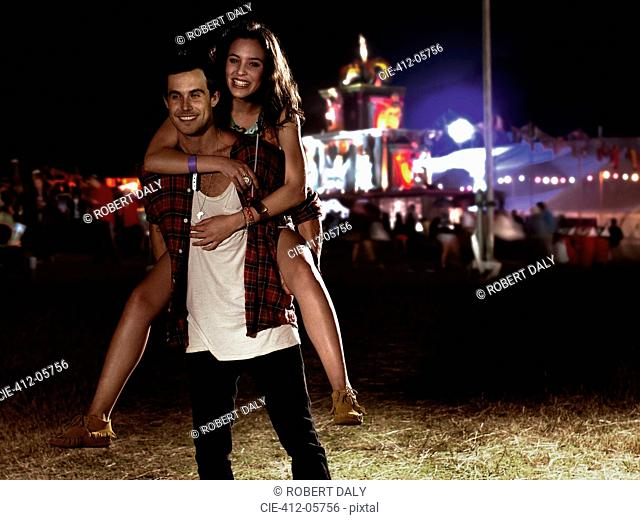 Portrait of man piggybacking woman at music festival