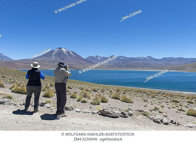 Tourists photographing the Miscanti volcano 5640 m (18,504 ft. ) and Miscanti lagoon in the Los Flamencos National Reserve near San Pedro de Atacama in the...
